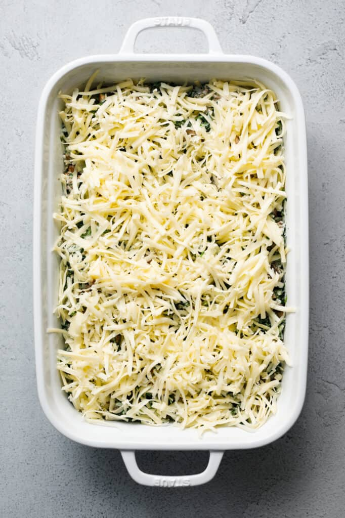 A casserole dish filled with Spinach Fandango topped with shredded white jack cheese.