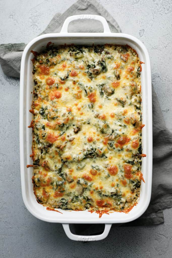Spinach Fandango is a hearty casserole of cheese, spinach, beef and rice in a large casserole dish.