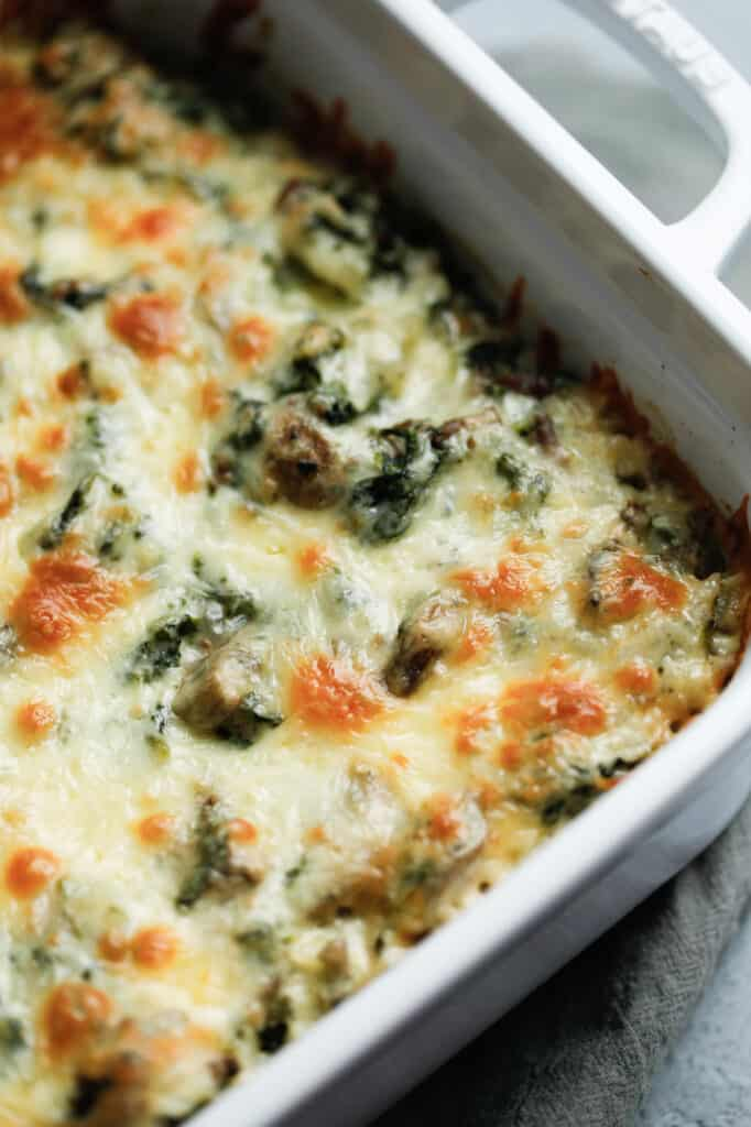 A closeup of the cheese topping on a cheesy spinach and beef casserole topped with colby jack cheese.