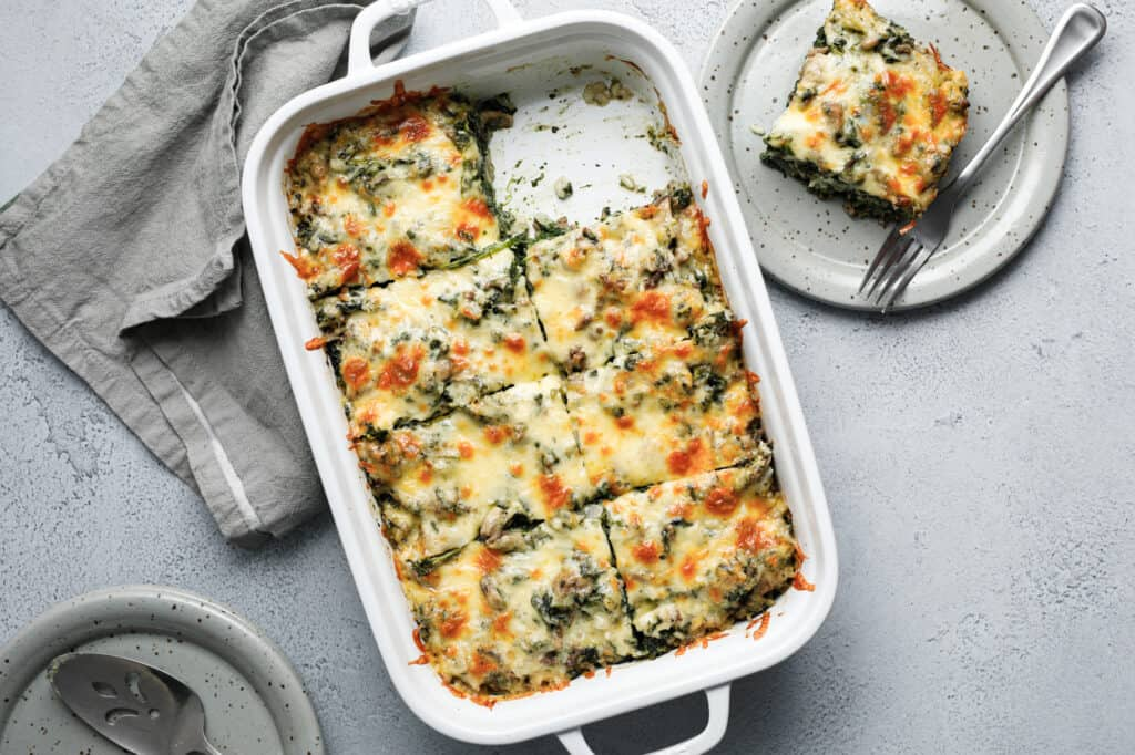 A large dish filled with a spinach, cheese and beef casserole with a piece taken out and put on a grey plate with a fork
