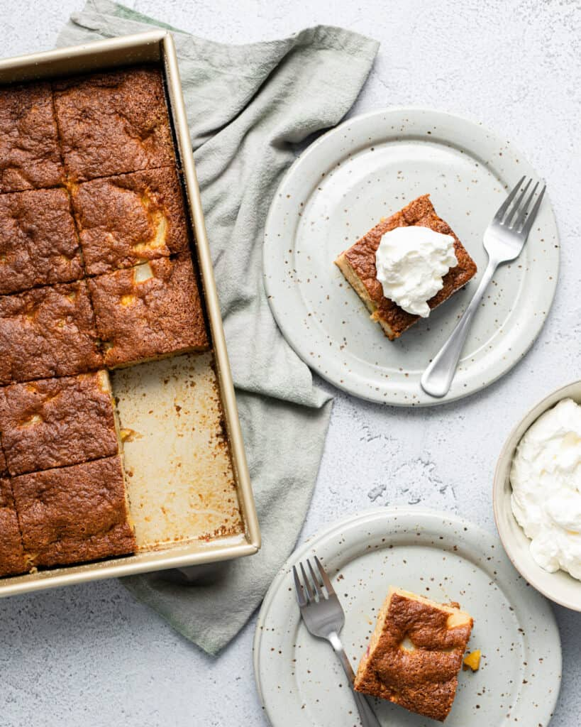 a sheet pan of fruit cocktail cake with two slices cut out and placed onto plates with forks and whipped cream