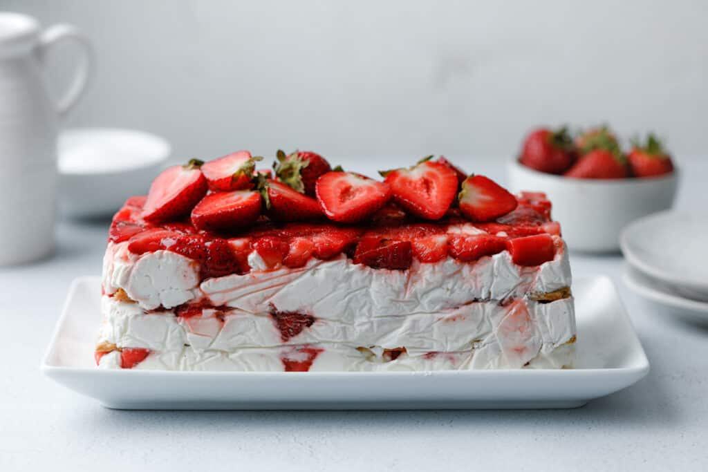 A layered icebox cake dessert with graham crackers, strawberries and cream cheese whip on a white plate surrounded by strawberries and plates