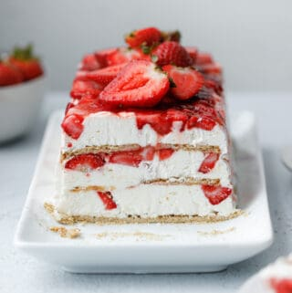 A layered icebox cake dessert with graham crackers, strawberries and cream cheese whip on a white plate surrounded by strawberries and slices of cake