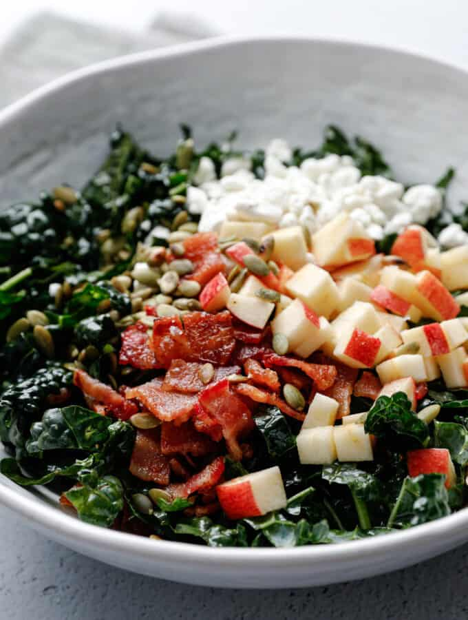 A white bowl filled with kale salad topped with goat cheese, bacon, pepitas, and apple