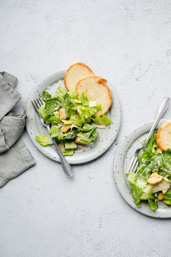 Overhead image of two plates of Caesar Salad on plates with forks and a napkin