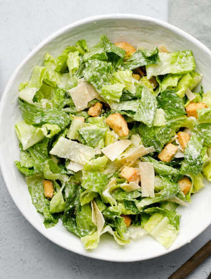 overhead view of a bowl of Caesar salad with tongs and dressing on the side