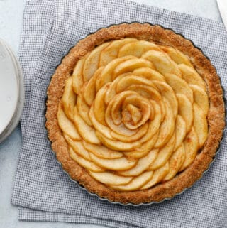 Overhead view of an apple tart with spiraled apples, with a knife to the side and plates with forks ready to serve the pie