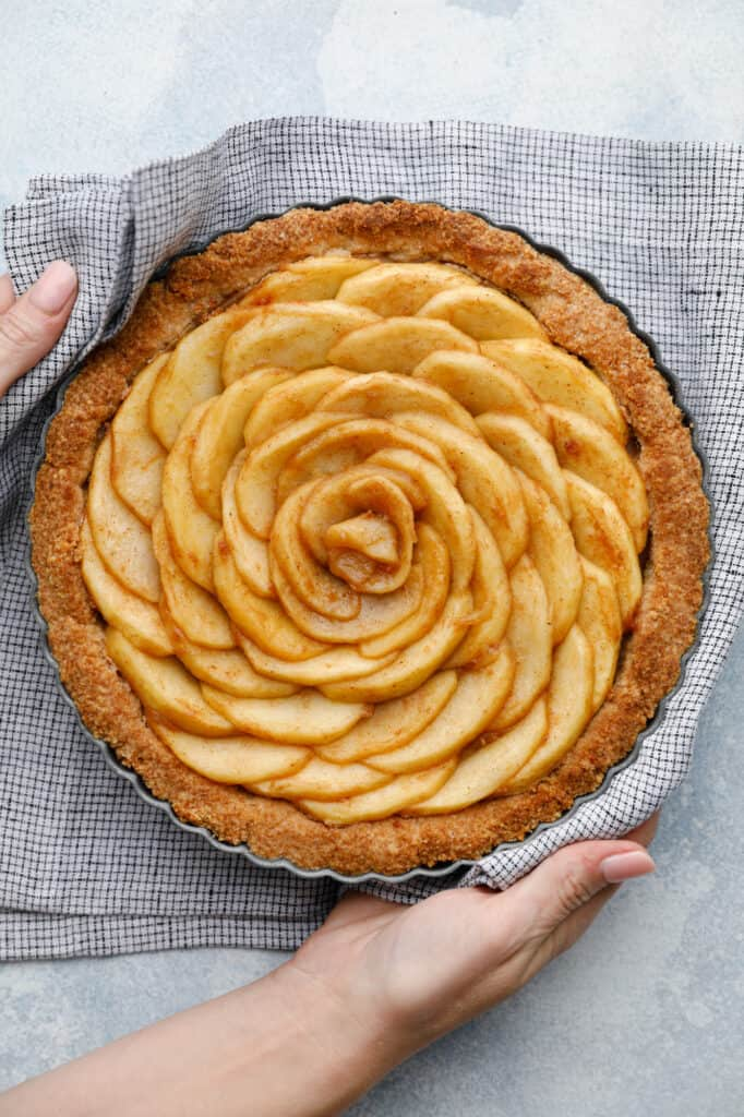 Overhead view of an apple tart with spiraled apples fresh out of the oven being held with two hands an a kitchen towel
