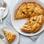 overhead image of an apple tart sliced with a slice on a separate plate