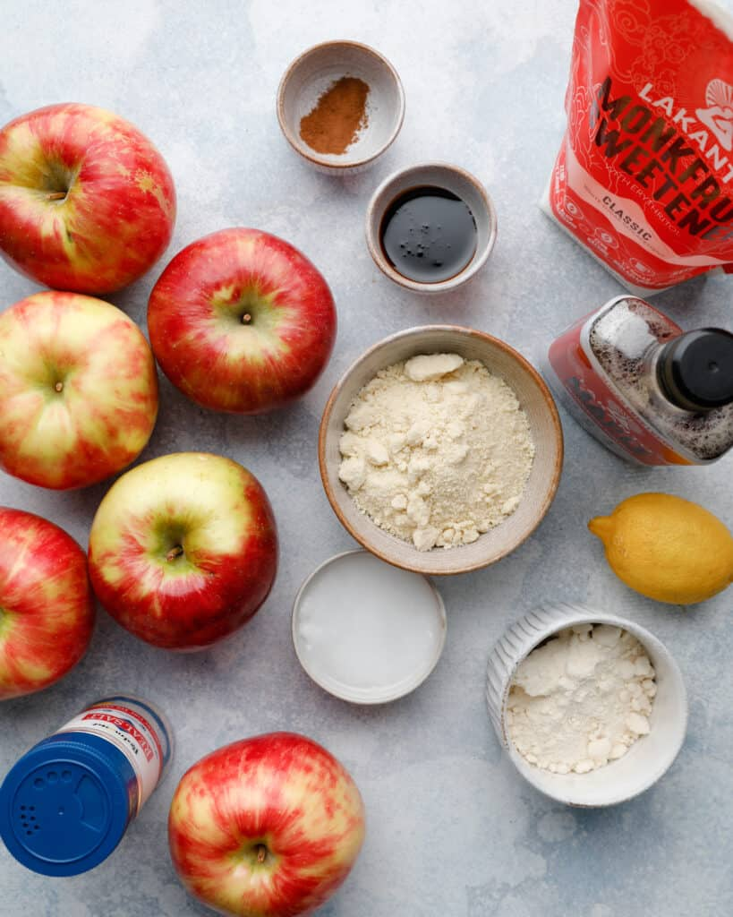 Overhead view of ingredients to make a gluten free apple tart including honeycrisp apples, monkfruit sweetener, almond flour and coconut flour