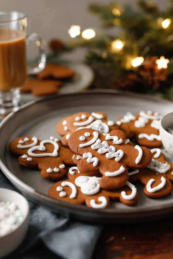 Gingerbread boys on a grey plate with silver sprinkles and sparkle lights in the background