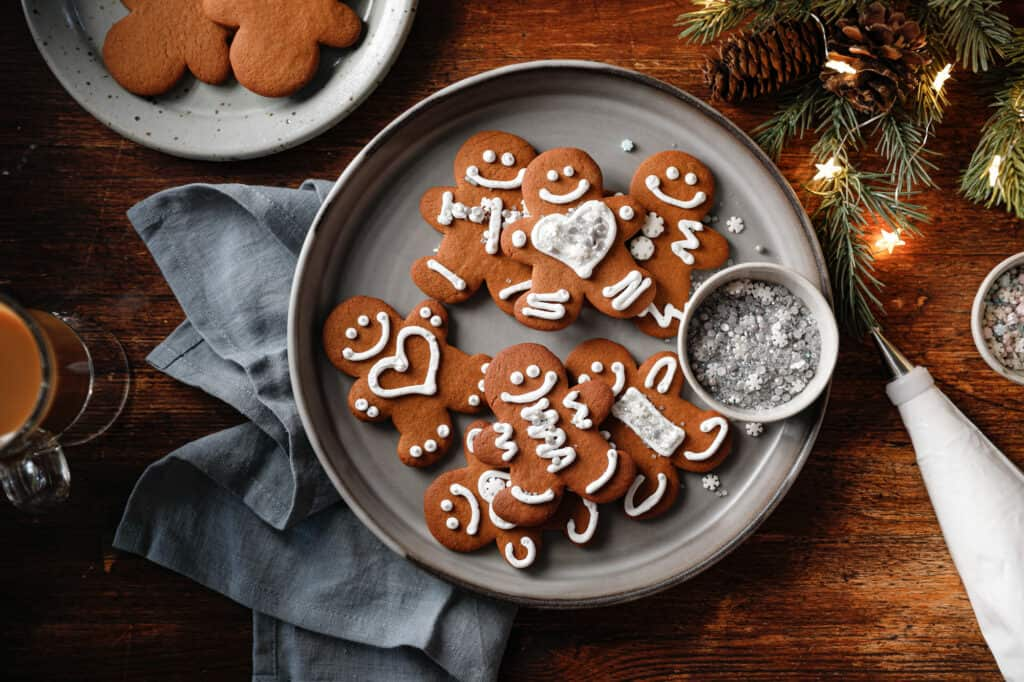 Overhead image of a plate of gingerbread cookies with holiday lights, sprinkles and a piping bag