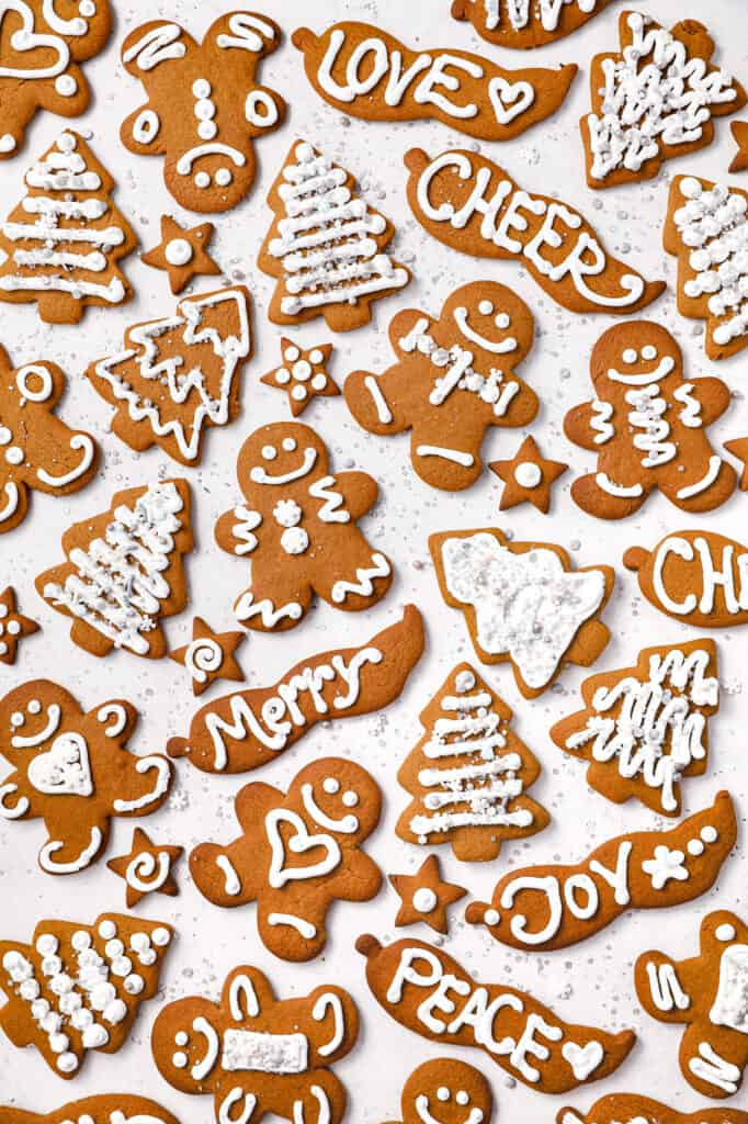 Overhead image of a variety of gingerbread cookies decorated with white royal icing