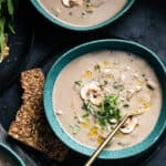 Overhead view of three bowls of cream of mushroom soup with garnish, a spoon and a side of seed crackers