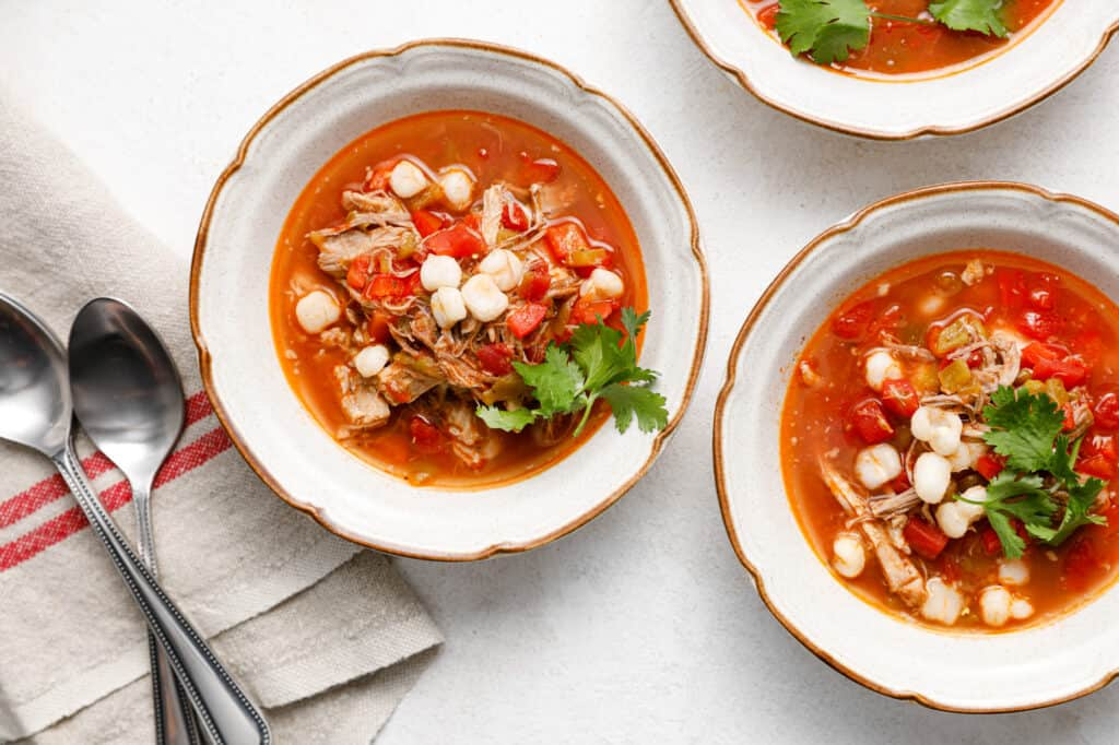 overhead image of bowls of red posole with pork and hominy