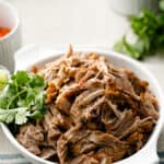 Pulled Pork Carnitas in a serving bowl with fresh cilantro