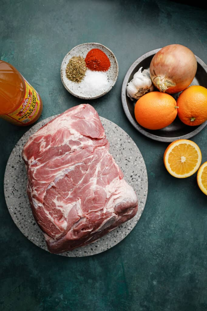Ingredients for Instant Pot Pork Carnitas on a table with oranges, garlic and spices