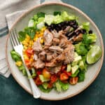 overhead view of a salad with shredded pork, lettuce, tomatoes, avocado and black beans