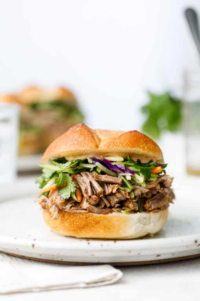 Head on shot of a pulled pork sandwich with broccoli slaw on a white plate