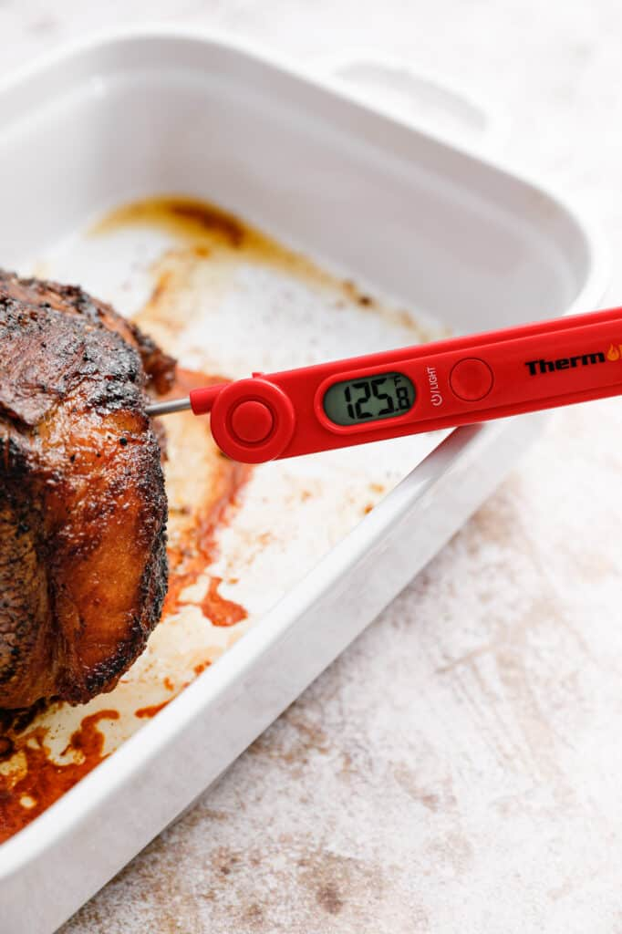 the beef out of the oven and showing a meat thermometer with 125F as the temperature