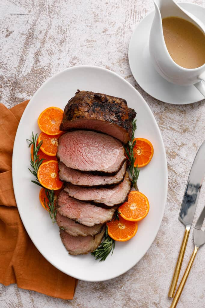 Overhead view of a slice beef roast on a platter with citrus and rosemary.