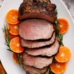 overhead view of a beef roast, sliced and surrounded by citrus and rosemary