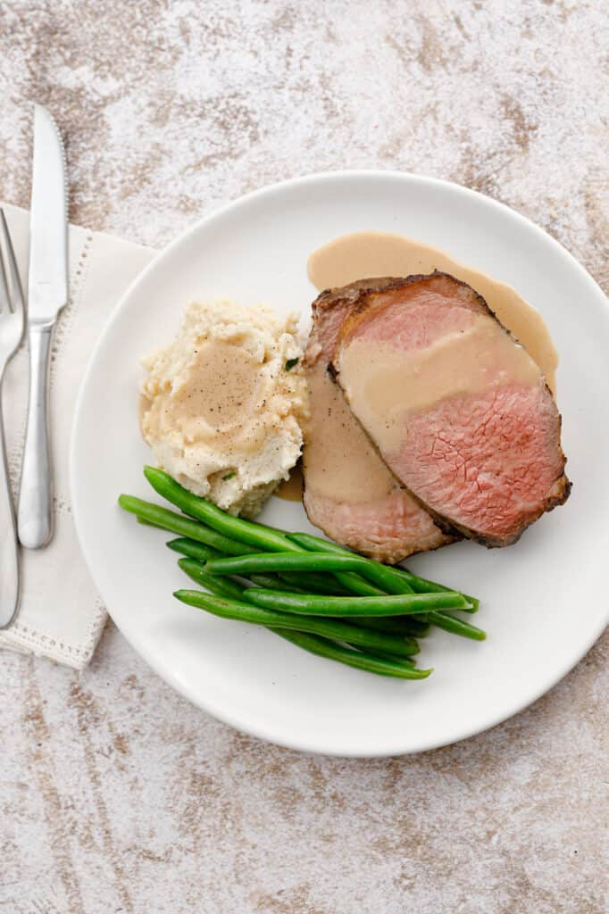 overhead shot of a plate of beef, mashed potatoes and green beans
