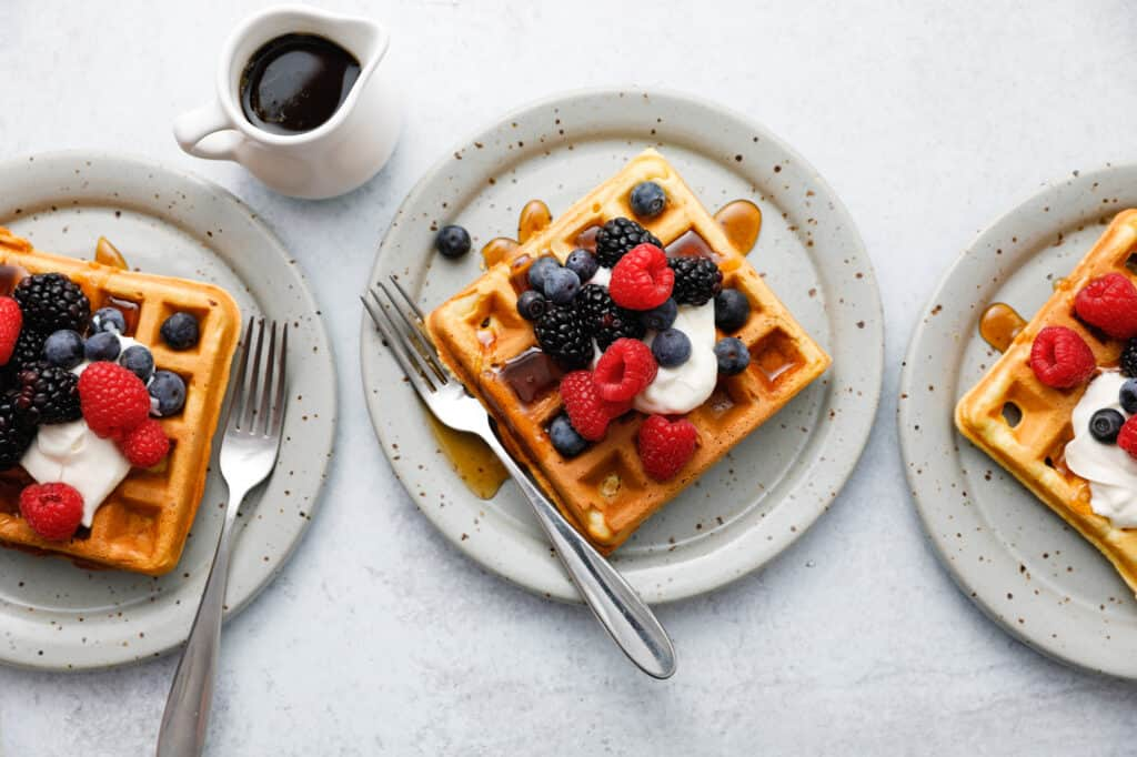 Three waffles seen overhead on plates with forks topped with sour cream and berries with maple syrup being drizzled on
