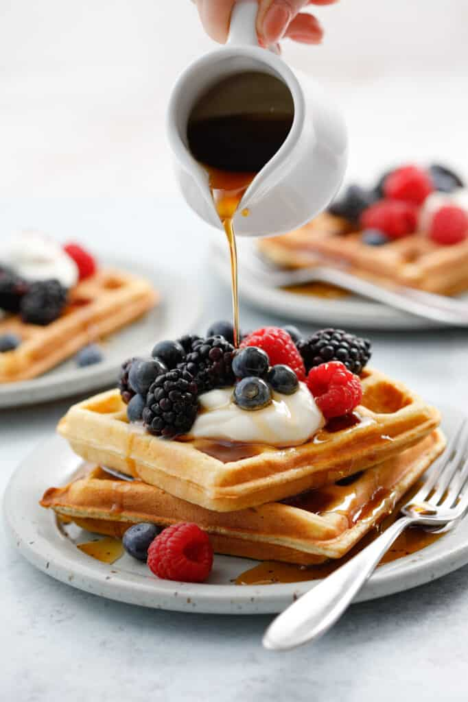 A stack of two waffles topped with sour cream and berries with maple syrup being drizzled on