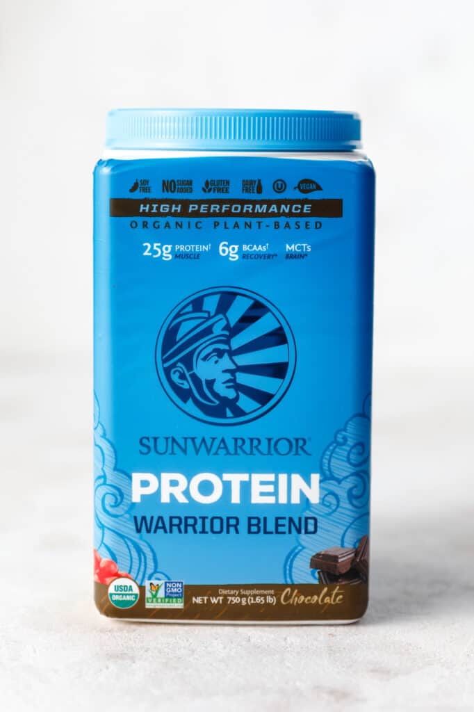 A container of sun warrior protein powder in chocolate flavor