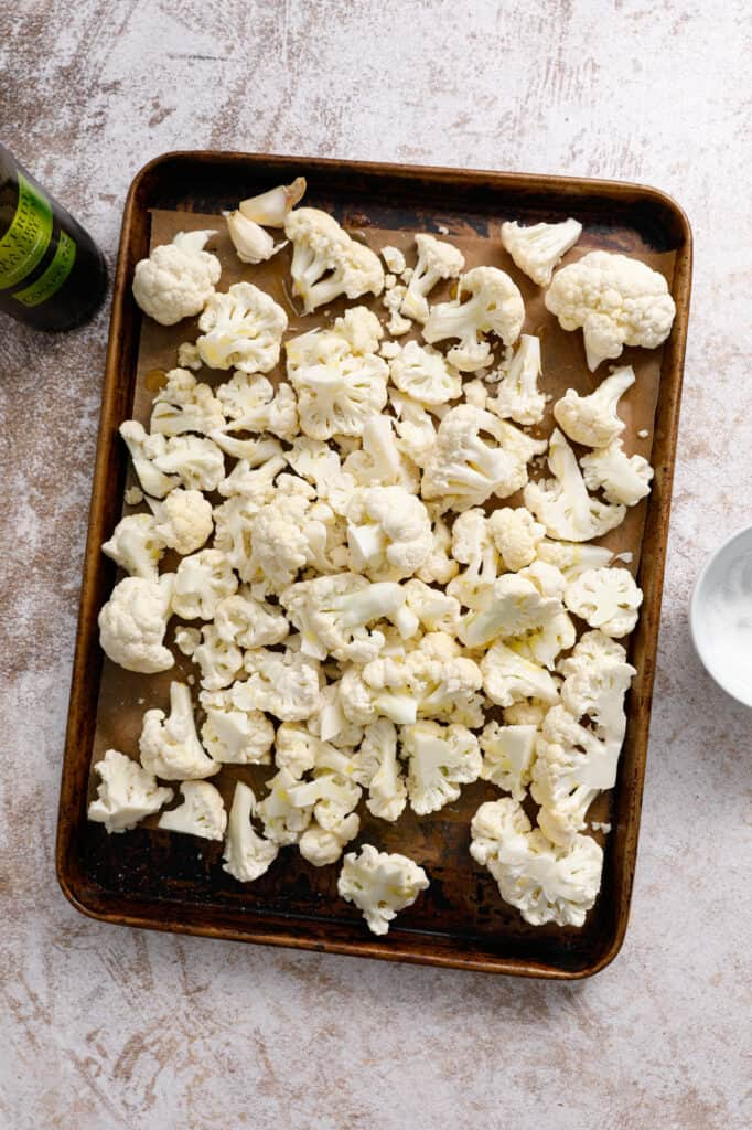 overhead view of a baking pan with cauliflower florets tossed in olive oil and salt