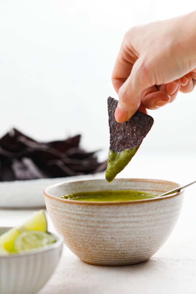 side view of dipping a chip in salsa with chips and limes in the background