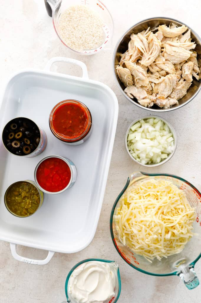 The ingredients for southwest chicken and rice casserole with chicken, onions, cheese, sour cream, tomatoes, salsa, chilies, rice and olives.