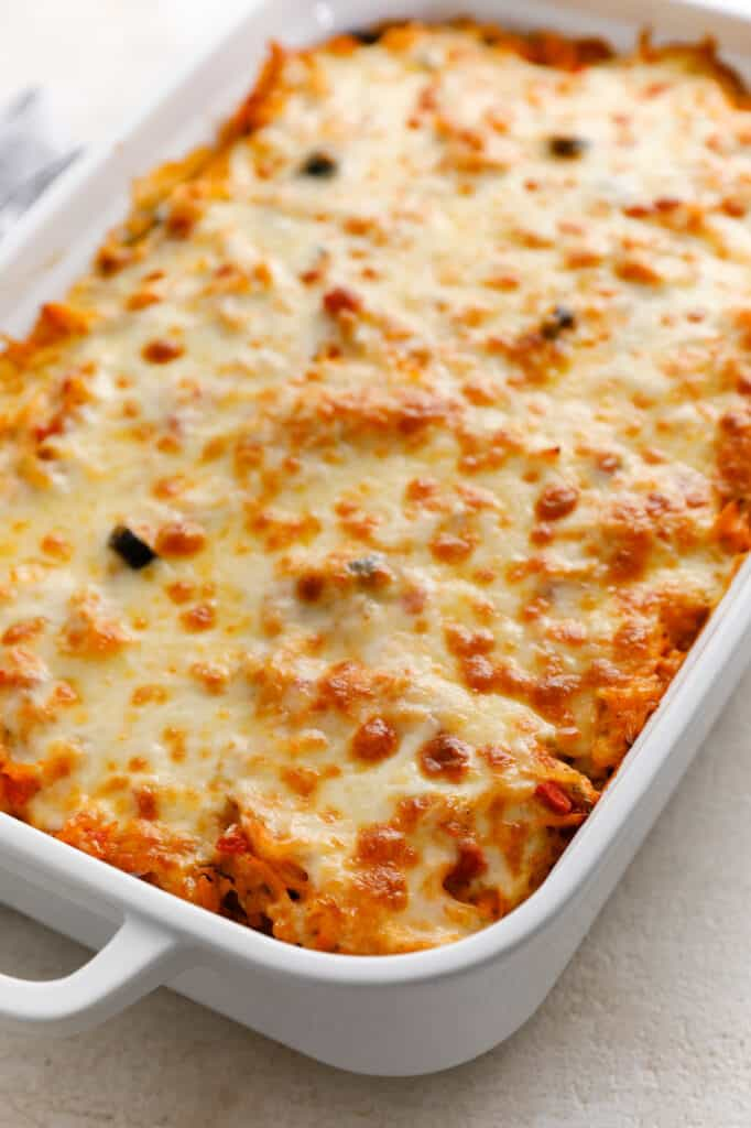a casserole dish full of chicken and rice casserole topped with cheese, browned from baking in the oven