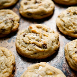 image of a close up of a chocolate chip cookie with flake salt on a cookie sheet