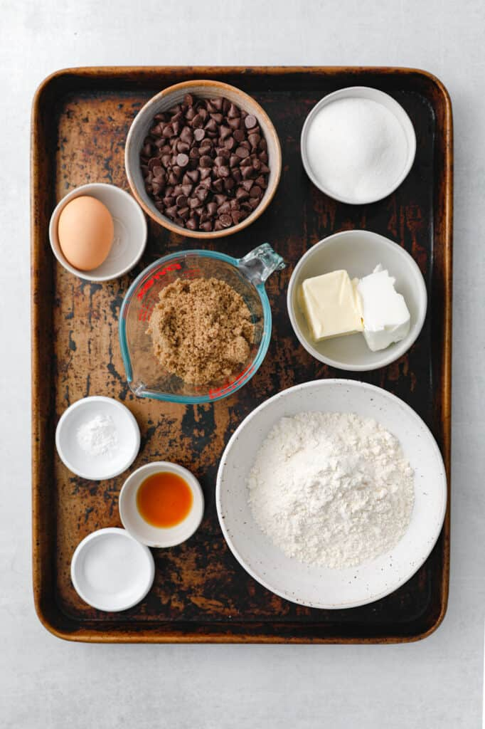 overhead view of all the ingredients to make classic chocolate chip cookies: butter, shortening, flour, sugar, brown sugar, vanilla, baking powder, salt, egg and chocolate chips