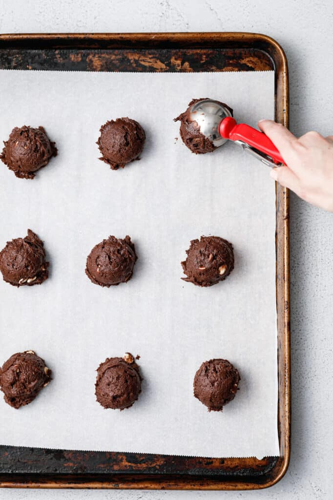 Scooping Chocolate Cookie Dough onto a baking sheet