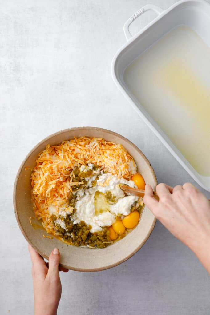 a large bowl mixing together the ingredients: eggs, cottage cheese, chilis, flour, baking powder and shredded cheese