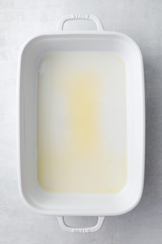 A pan prepared with melted butter ready to make the overnight egg casserole