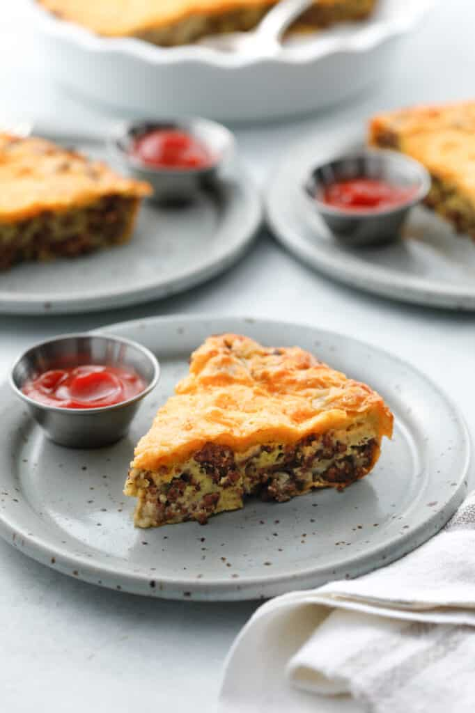 A slice of Impossible Cheeseburger Pie on a plate with a fork and a side of ketchup with other plates in the background