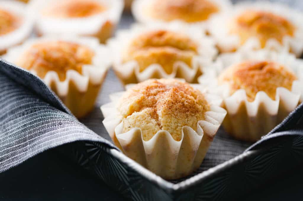 sweet cake snickerdoodle muffins are topped with cinnamon and sugar in cute cupcake liners