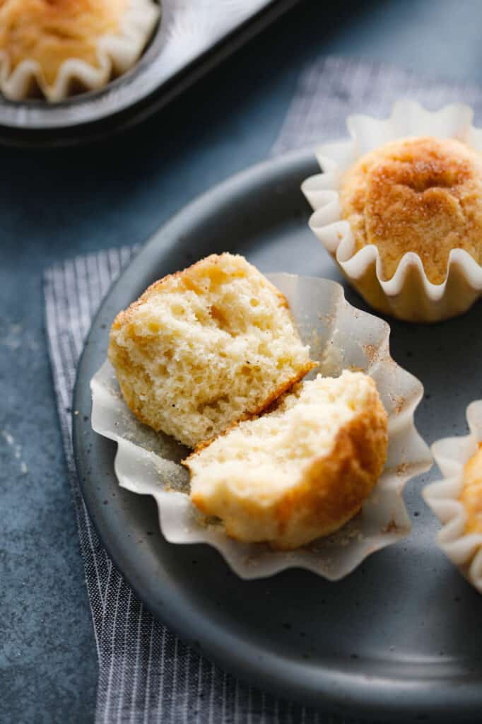 snickerdoodle muffins cut in half to show the soft cake-like interior