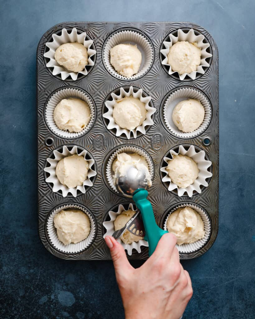 measuring out scoops of snickerdoodle muffin batter into a muffin tin