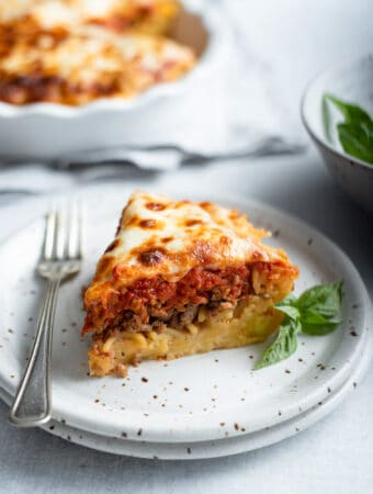 a slice of spaghetti pie on a plate with a fork, a spaghetti crust topped with ground Italian sausage, marinara and mozzarella