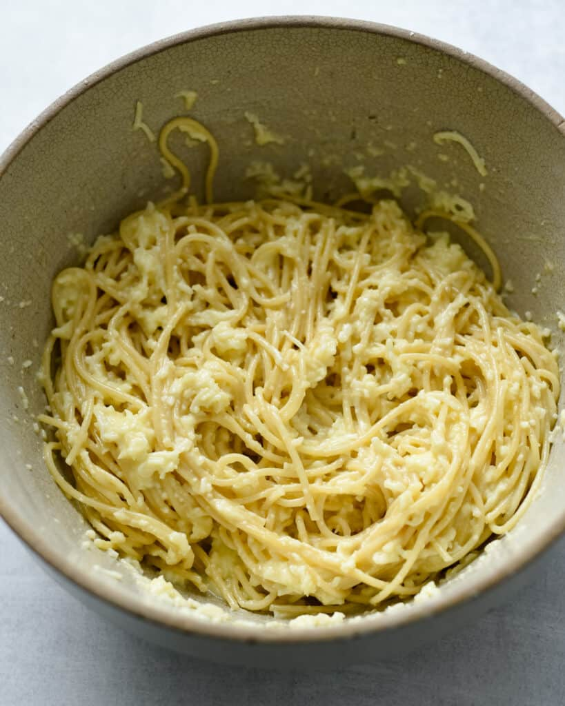 The spaghetti pasta in a bowl with egg and cheese before it becomes the crust