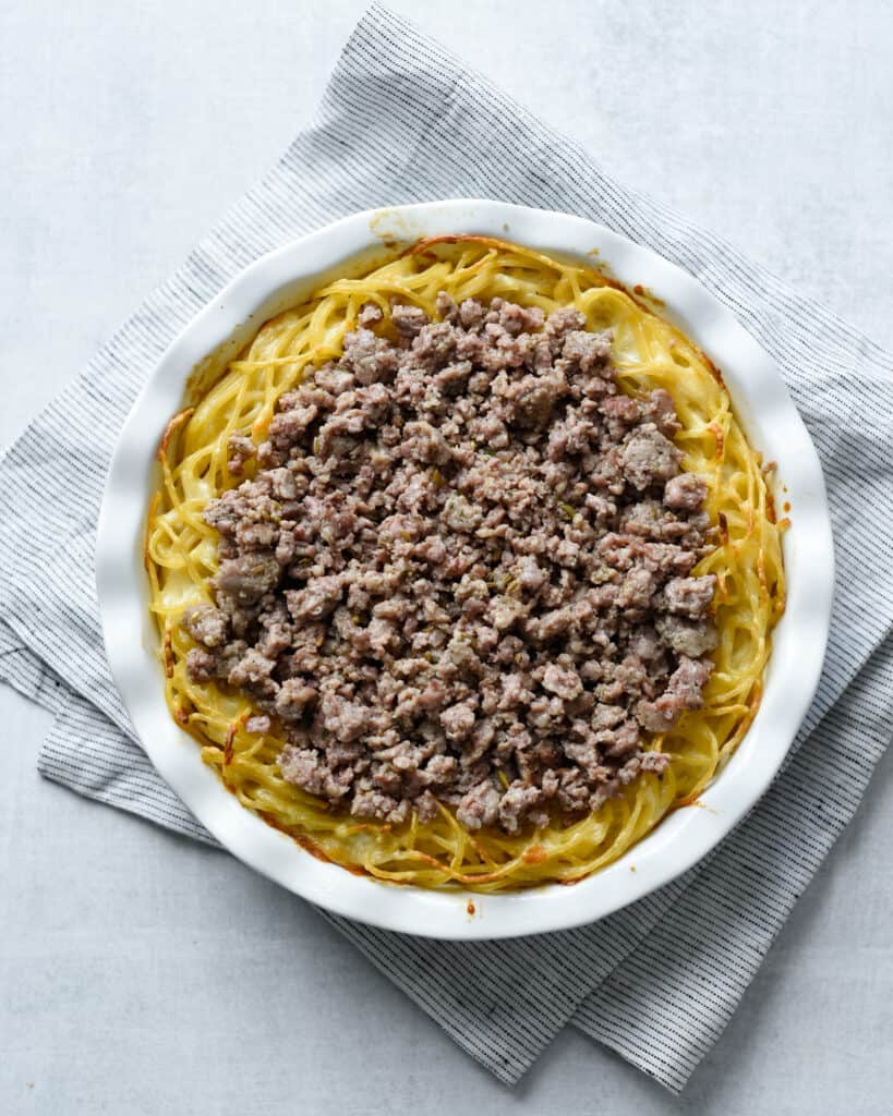 top your spaghetti pie with your favorite toppings. we like ground Italian sausage