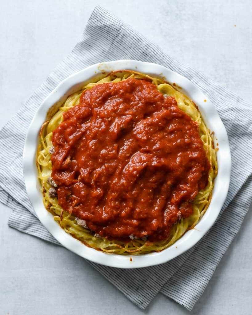 spaghetti pie in process being topped with marinara sauce