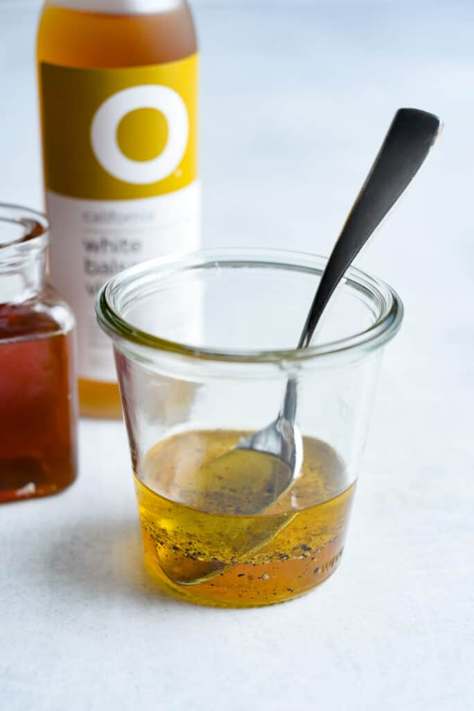 easy white balsamic vinaigrette in a glass jar next to honey and vinegar