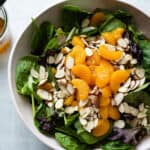 A large bowl filled with mandarin oranges, spinach, almonds and with a side of vinaigrette