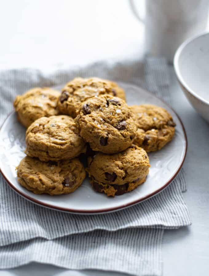 pumpkin chocolate chip cookies on a plate on a blue napkin next to a white mug